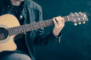 close up of man playing guitar.